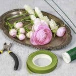 Florist at work. Steps of making wedding wreath with pink rose, ranunculus and white